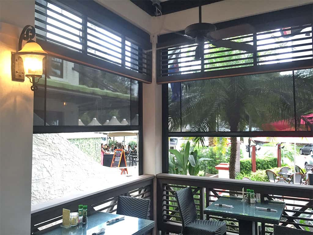 motorized restaurant sun shades half lowered see through material outside business patio tables and chairs sconce