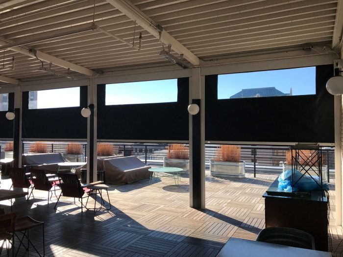 motorized retractable patio shades half lowered clear vinyl window hotel rooftop patio sunny day