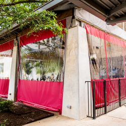 red enclosures clear vinyl window commercial product outside view restaurant patio manual roller shades