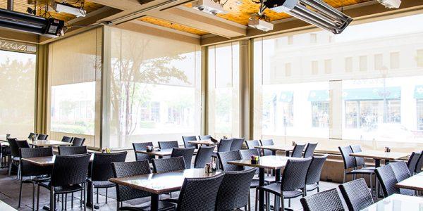custom beige patio sun shades with clear vinyl windows and climate control system deployed glorias interior patio garland texas restaurant furniture